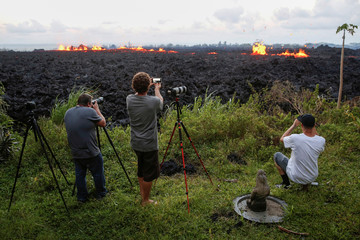 Photographers take photos of a fissure on the outskirts of Pahoa