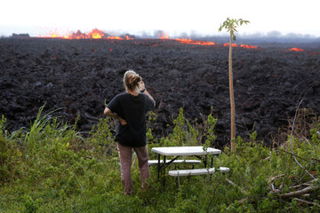 Jolon Clinton, 15, takes a photo of a fissure near her home on the outskirts of Pahoa