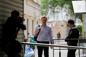 Russian opposition leader Navalny walks before entering a court building in Moscow
