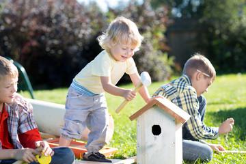 Children boys make a birdhouse for the birds in the garden of a summer sunny day