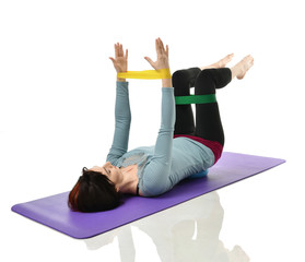 Woman exercising doing postnatal workout. Female fitness instructor working out with a rubber resistance band isolated on white