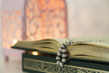 Koran and rosary on the white background with pink candle for Islamic concept. Holy book Quran for Muslims for Ramadan and three months.