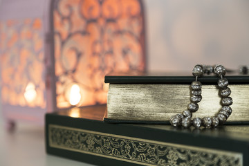 Koran and rosary on the white background with pink candle for Islamic concept. Holy book Quran for Muslims for Ramadan and three months. Wall mural