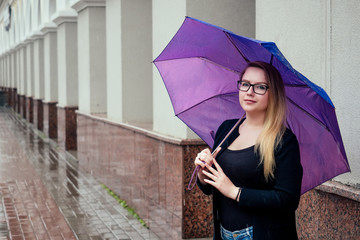 Smiling blond girl with a purple umbrella on a background of columns in autumn in the rain. Girl with glasses