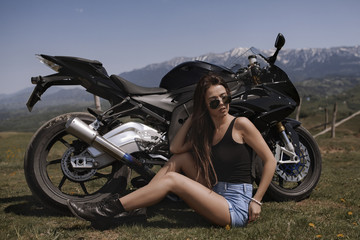 Beautiful woman posing with a motorcycle in mountain scenery