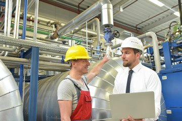 Ingenieur/ Manager und Arbeiter bei einer Besprechung in einer Industrieanlage // Engineer/manager and worker at a meeting in an industrial plant