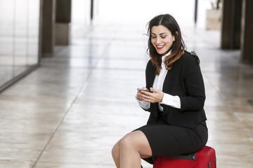 Manager vestita con un tailleur nero guarda il suo cellulare sorridente, seduta sopra una valigia rossa aspettando - sfondo corridoio esterno in marmo