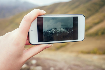 girl holding a phone and photographing the landscape