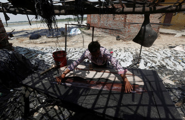 A worker makes leather belts outside a tannery on the banks of river Ganges in Kanpur