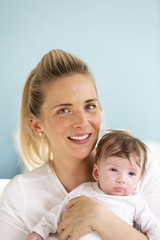 young, beautiful and blond mother is holding her baby in her arms