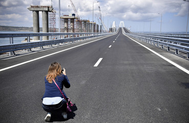A woman takes pictures prior to a ceremony opening a bridge, which was constructed to connect the Russian mainland with the Crimean Peninsula across the Kerch Strait