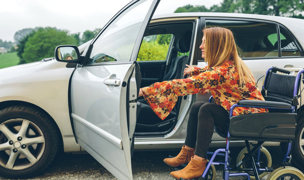 Young woman in a wheelchair getting on the car