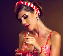 Pin up girl drink bloody Mary cocktail. Pin-up retro female style. Girl wearing red dress seduces men. Surprise party for your girlfriend. She's drunk with alcohol.