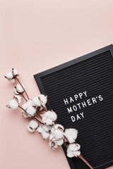 Black letterboard with white plastic letters with quote Happy Mother's Day, and cotton on pink background with copy space.