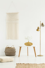 Beige DIY macrame on a white wall, wooden furniture and golden decorations in a boho living room interior