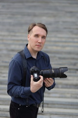 Work of the photographer. A serious man holds the camera. Journalist. Paparazzi