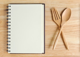 empty wood plate with notebook open and spoon ,frok