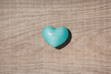 Blue heart shape over wooden table. Symbol of valentine day for background use. Concept of love and romance.