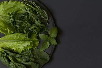 Fresh green on a plate of slate on a black background.