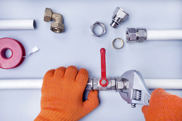 Professional male plumber of tightening the screw with a spanner.Repair,construction concept.