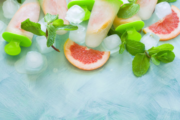 Homemade grapefruit popsicles with grapefruit slices on a mint wooden background. Top view. Copy space. Flat lay