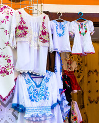 Beautiful bright ethnic shirts and tablecloths with traditional Hungarian embroidery in a street store.