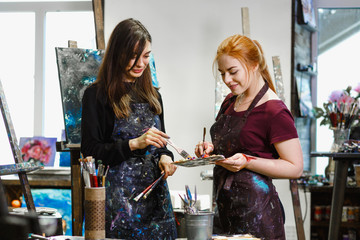 Two artists talking in the art Studio. The girl works in an art Studio. Bright Art Studio with large Windows. .