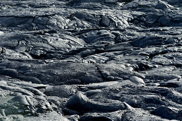 Smooth, undulating surface of frozen pahoehoe lava. Frozen lava wrinkled in tapestry-like folds and rolls resembling twisted rope on Big Island of Hawaii.