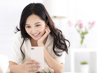 young woman sitting on couch and watching smart  phone