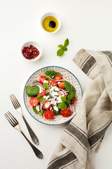Tomatoes, spinach leaves, red onions and feta cheese salad on a light ceramic plate. Selective focus. Top view.