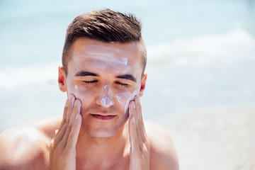 Attractive man putting tanning cream on his face, closing his eyes, takes a sunbath on the beach. Healthcare.