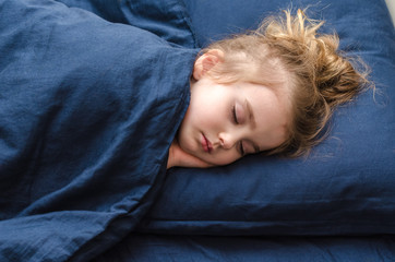 little pretty girl is sleeping soundly on blue bedding