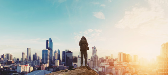 a man with backpack standing on the mountain enjoying beautiful sunrise in the city