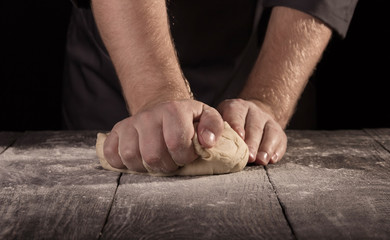 Baker's hands kneaded of dough on an wooden surface sprinkled with flour