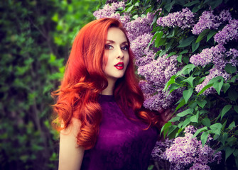 Beautiful young woman and lilac. Sensual red-haired girl