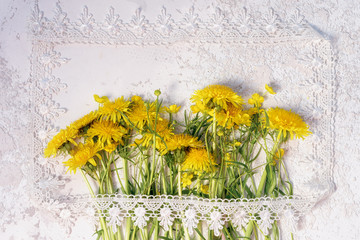 bouquet of wildflowers, dandelions and buttercups, in the style of a rustic postcard on a white textured cement background in a picture frame made of lace. copy space for your greeting text.