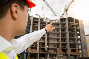 Closeup image of male architect pointing with finger and showing new building under construction