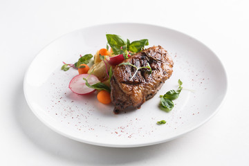 Roast duck breast with vegetables. Served on a white plate