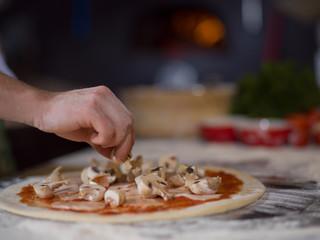 chef putting fresh mushrooms on pizza dough