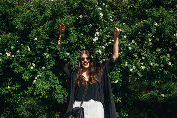 beautiful Stylish Hipster Girl with beautiful  hair having fun,falling in floral bushes in sunny day. Boho Woman with sunglasses in fashionable outfit, smiling and enjoying day in garden