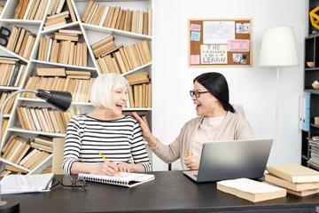 Great work. Joyful senior woman writing down while laughing with tutor