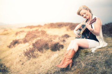 Young happy woman sitting in a field and playing guitar