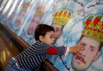The son of one of the Egyptian Christians who were beheaded in Libya by Islamic State in 2015, touches his father's picture at a church in al-Our village south of Cairo