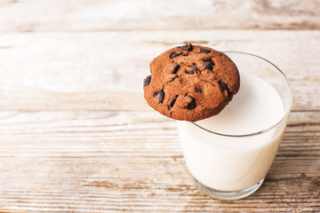 chocolate chip cookies and a glass of milk on an old board, top view