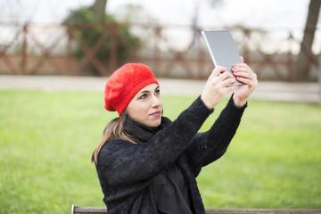 ragazza Mora vestita di nero con una cuffia rossa in testa si fa un selfie con un tablet  - sfondo prato verde