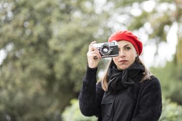 ragazza Mora vestita di nero con una cuffia rossa in testa ci fa una fotografia con la sua reflex immersa in un parco