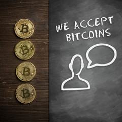 """Bitcoin Münzen auf Holzuntergrund mit Wandtafel und Hinweis """"We accept Bitcoins"""""""