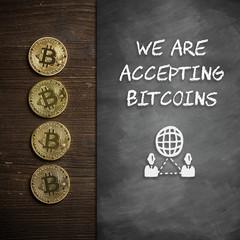 """Bitcoin Münzen auf Holzuntergrund mit Wandtafel und Hinweis """"We are accepting Bitcoins"""""""