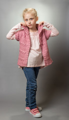 Charming little fashionista in jeans on gray
