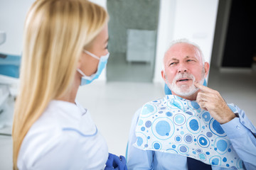 Dentist with sterile mask and dental instruments held exam teeth of patient